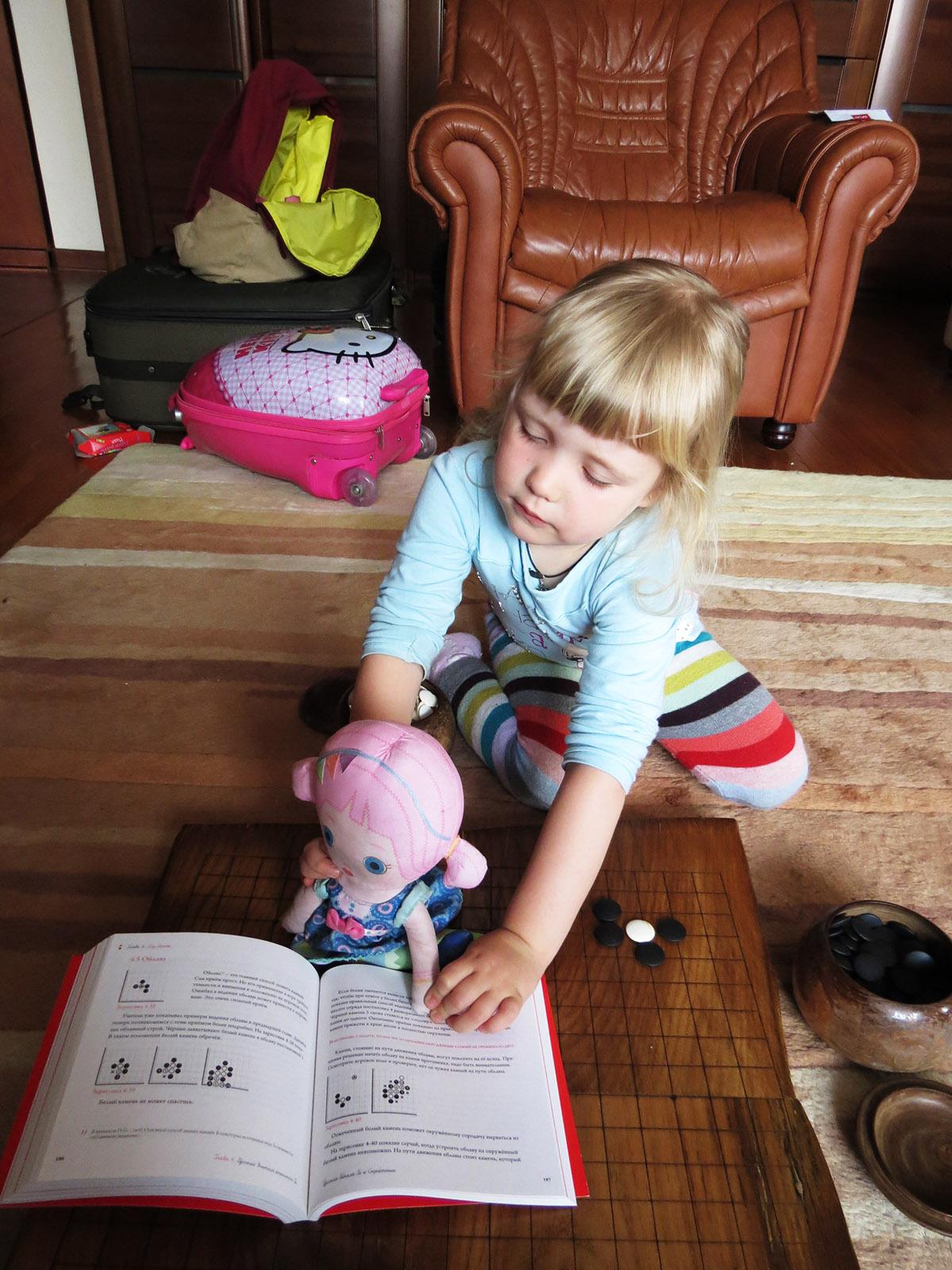 Кукла читает учебник